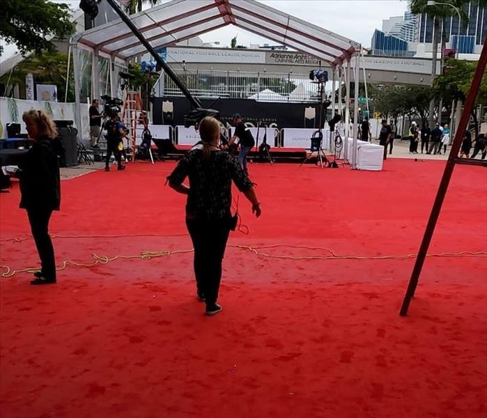 A red carpet with video equipment and people in front of a large tent and building.