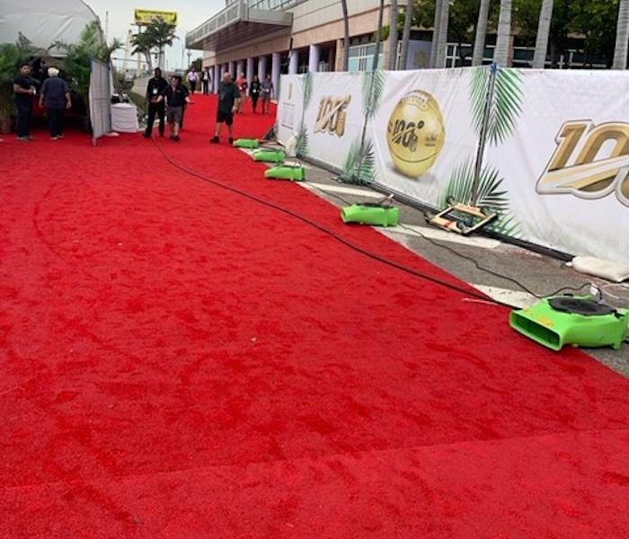 A red carpet with SERVPRO equipment lined up on the carpet, in front of a large building.
