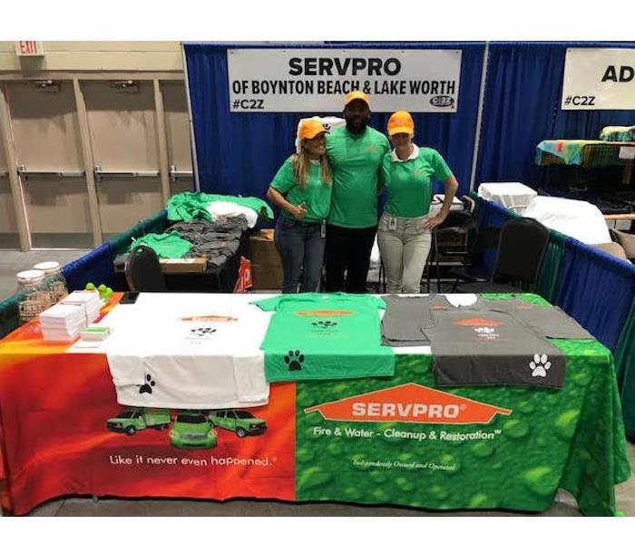 Three SERVPRO employees standing behind a both.