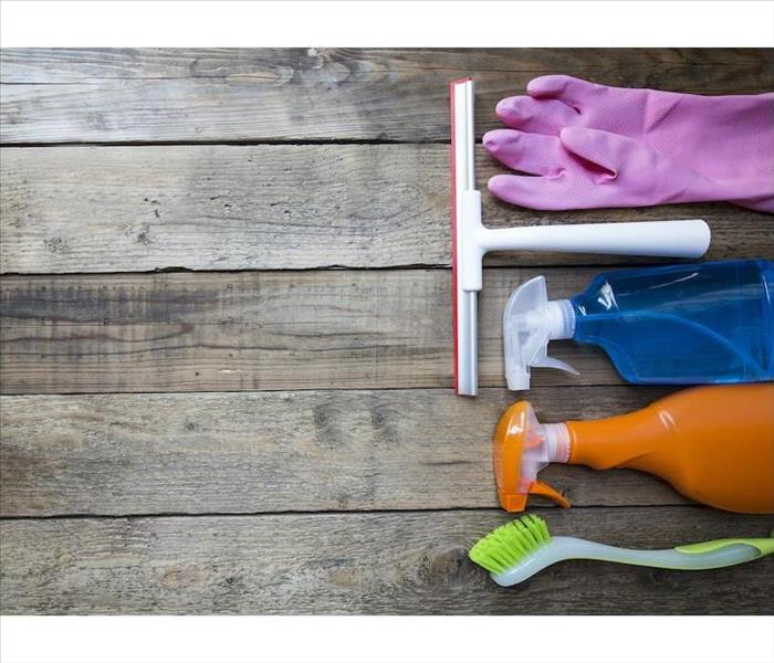 bottles, gloves and brushes laying on a wood surface