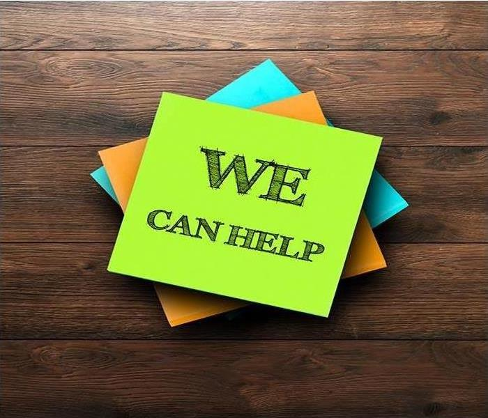 sticky notes with 'we can help' written on the top sitting on wooden table