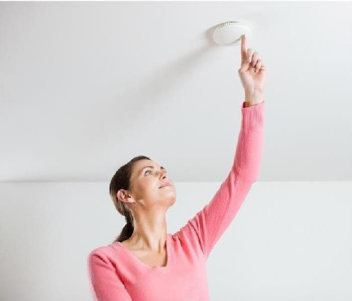 Woman  testing ceiling mounted smoke alarm